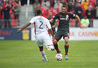 Toronto, Ontario - May 3, 2014: Toronto FC forward Gilberto #9 and New England Revolution defender Andrew Farrell #2 in action during a game between the New England Revolution and Toronto FC at BMO Field.