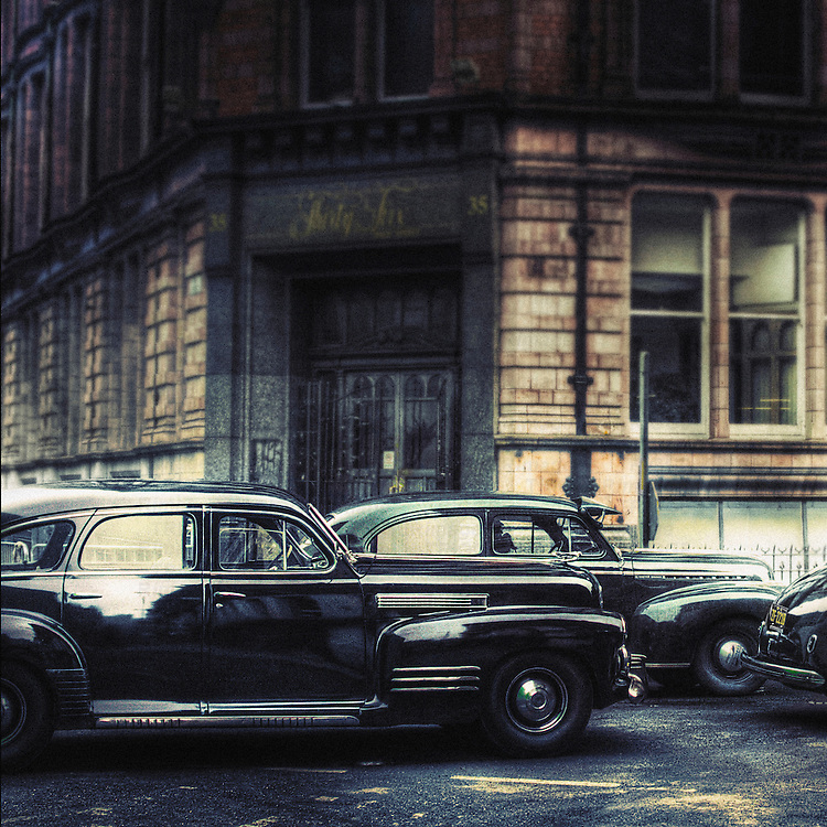 A 1941 cadillac series-61 and a 1941 chevrolet master deluxe sedan parked in the street with full period look