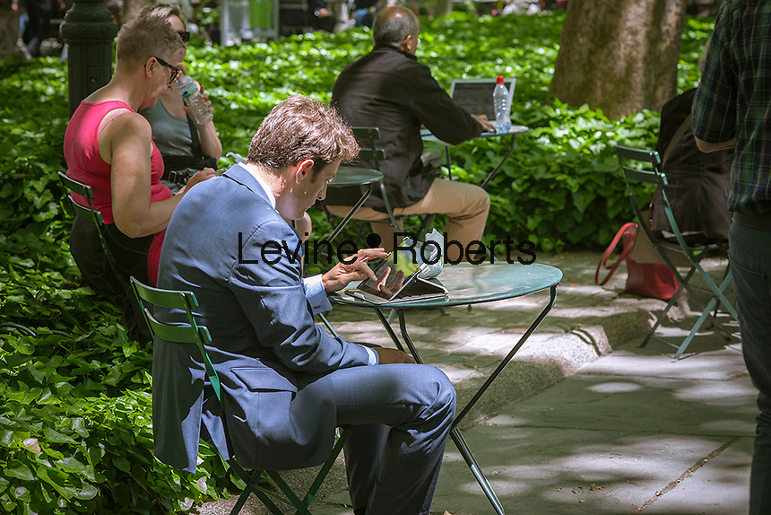 A visitor to Bryant Park in New York uses his tablet computer on Tuesday, June 4, 2013.  (© Richard B. Levine)