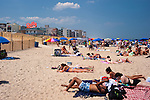 Couples and families relax on the beach while working on their tans.  Rehoboth Beach, Delaware, USA.