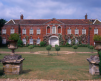Distinctive red brick buildings face the garden