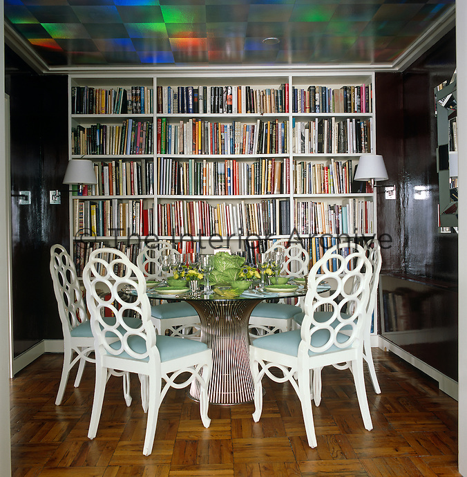 Full height bookcases and a holographic paper on the ceiling together with lacquered aubergine walls give an illusion of space in the library/dining room