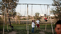 Women play with their children on a set of decrepit swings in a park in Garden City, Kansas. They are the families of the many migrants who have come to the town to work at the Tyson meat packing plant. This facility kills and processes between five and six thousand beef cattle every day. Kansas dominates the American beef industry, producing 25% of all beef raised in the USA. However, the industry is heavily dependent on cheap immigrant labour. Behind the park is a line of trucks that deliver beef cattle for slaughter.