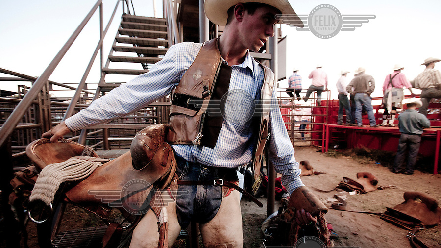 A rodeo rider carries his saddle into the stadium in Dodge City, Kansas.