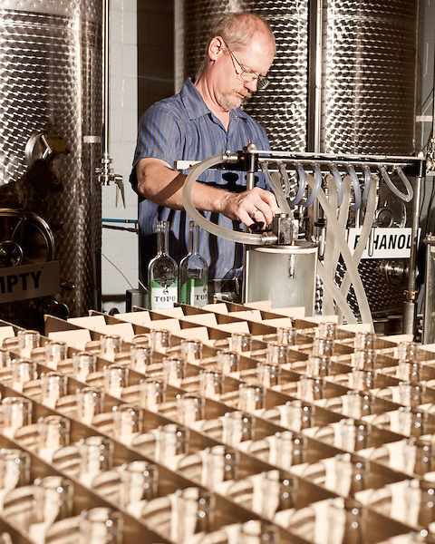 June 18, 2013. Chapel Hill, North Carolina<br />  Head distiller George Dusek fills bottles of TOPO Gin with a repurposed milking machine.<br />  TOPO, Top of the Hill Distillery, the brainchild of owner Scott Maitland and Spirit Guide Esteban McMahan, is located in the old N&amp;O Building on Franklin Street. Making gin, vodka and American whiskey from locally sourced wheat, they are one of the few distilleries bringing  organic liquor to ABC shelves around the state.