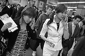 Two young women have conversations on their mobile telephones as they walk in a busy street outside Shinjuku Station, Tokyo, Japan.