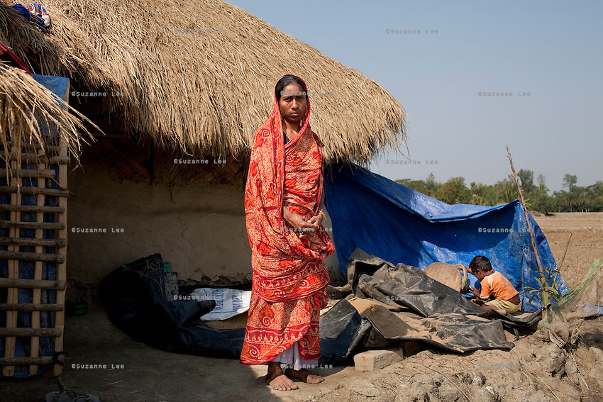 Widow Mamata Mandol (center), 26, stands for a portrait with two of her 3 young children at her home on Gosaba island, Sundarban, West Bengal, India, on 18th January, 2012. While her husband was killed while fishing, tigers have been known to swim, sometimes underwater, to the village to hunt humans. A successful Royal Bengal tiger breeding program has increased their numbers but decreased the number of husbands. There are now an estimated 3,000 widows in the villages where their husbands, have been killed by tigers. Photo by Suzanne Lee for The National (online byline: Photo by Szu for The National)