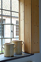 New, simple pitch-pine shutters have been created to blend with the old farmhouse windows