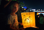 A girl carries a floating candle lantern to the river on August 6, 2015, in Hiroshima, Japan. The lanterns, thousands of which were launched on the 70th anniversary of the atomic bombing of the city, carry handmade messages and drawings, conveying each person's prayers for peace and comfort for the victims of the violence.