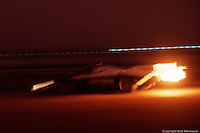 Trailing a plume of flame from the turbo, the Porsche 962 of Al Holbert, Derek Bell and Al unser, Jr. streaks into the first hairpin of Daytona's infield road course enroute to a second place finish in 1985.