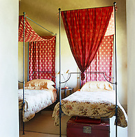 Twin wrought-iron beds have matching floral quilts and red polka dot bed hangings