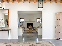 A cosy seating area off the entrance hall with concrete sofas built-in to the walls either side of an original fireplace