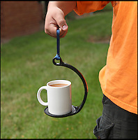 BNPS.co.uk (01202 558833)<br /> Pic: ThinkGeek<br /> <br /> A clever contraption has solved the age-old problem of spilling a mug of steaming hot tea or coffee when carrying it around.<br /> <br /> The SpillNot holder promises to do away with accidental splashes bringing an end to stained floor surfaces and scolded hands.<br /> <br /> The device is made up of a curved plastic arm and nylon carry-strap that is attached to a flat base, creating the perfect balance to stop anything from spilling.<br /> <br /> It can even be rotated around above head height, twirled in circles, or swung from side to side as it is carried without losing any liquid.<br /> <br /> The gadget uses centripetal force, a physics concept that means an object is forced to move in a curved line, to make the mug remain perfectly balanced.<br /> <br /> It can carry any mug or glass that is less than 4.5 inches wide and can be used by adults or children with hot or cold drinks.<br /> <br /> The SpillNot costs around &pound;10 from www.thinkgeek.com, a company based in Virginia in the USA.