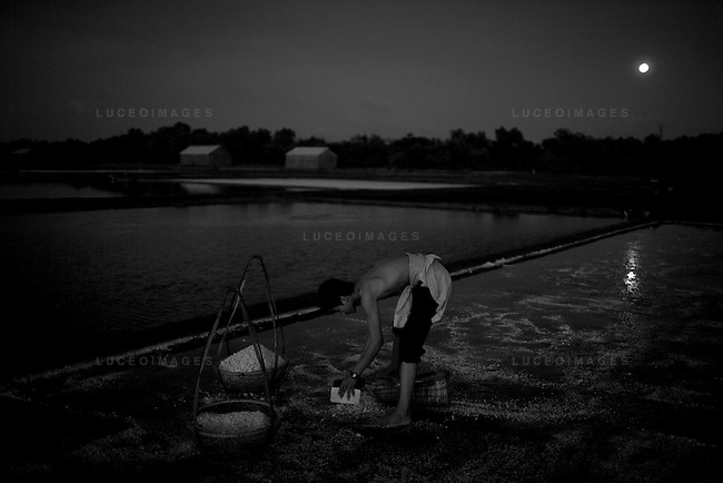 Salt people of Vietnam..Phong Quyen, 16, works late into the evening scraping salt into piles and filling baskets to be transported to a dry location...Farmers harvest salt cultivated in rice-patty like fields in Ben Tre, a village in southern Vietnam. The salt season usually begins in January and ends in March as these are the driest months. Photo taken Friday, March 21, 2008. Kevin German / kevin@kevingerman.com