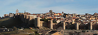 Panoramic View of the North West City Walls, 11th-14th century, Avila, Spain, with Cathedral, 11th-15th century, in the distance. Avila has superbly preserved walls built as fortifications against the Moors, an ancient cathedral, Romanesque churches, and is a pilgrimage destination due to its association with Carmelite nun St Teresa (1515-82), canonized 1622. The Old Town has been designated a UNESCO World Heritage Site. Photograph by Manuel Cohen.
