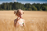Young Girl Blowing Bubbles in Cornfield, Estonia