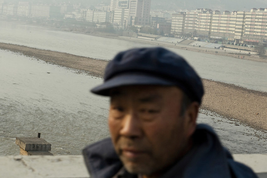 A chinese man on the bridge crossing the Yellow River in the fog of pollution in Lanzhou, China. <br /> <br /> -------<br /> Lanzhou, in the Gansu province is the most polluted cities of China and in the world's top ten for atmospheric pollution due to human activity. The town is situated between two hills along the Yellow River and the polluted clouds remains over the town. The sky is most of the time hidden by the pollution.