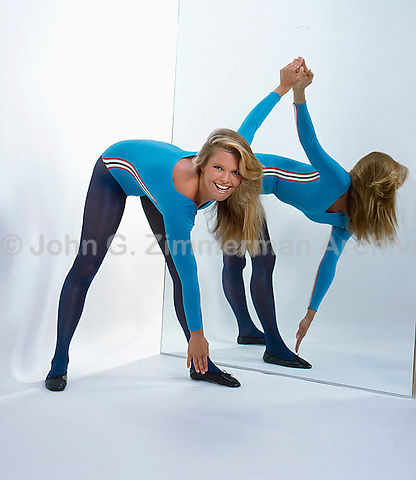 Christie Brinkley in blue leotard touches toes during exercise routine. 1982. Photo by John G. Zimmerman