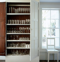 Glasses are arranged en masse in this tall built-in cupboard, where the shelves are covered with white self-adhesive plastic cloth