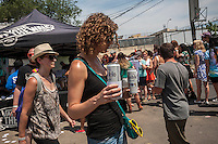 Hipsters drink beer and and buy food from food trucks at the annual Bushwick Block Party in the Bushwick neighborhood of Brooklyn on Saturday, July 27, 2013. Young adults came from all over to listen to music and to hang out with their friends and neighbors.  The party took place on Moore Street and was organized by the street's most well know resident, Roberta's Pizza. (©Richard B. Levine)