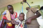 Mary Arcangelo (left) steadies her son, five-month old Mohamed, as Nyandeng Ring, a technician, weighs him during a periodic wellness exam at the St. Daniel Comboni Catholic Hospital in Wau, South Sudan.