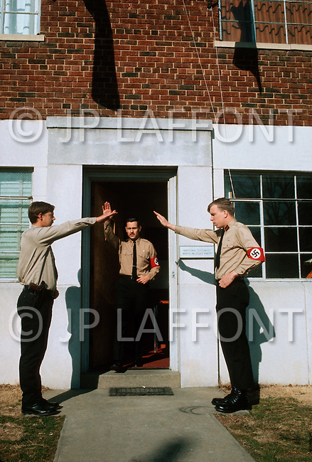 February 10, 1972, Arlington, Virginia. Matt Koehl, the comander of the White National Socialist Party leaving the headquarters, two troopers raise their hands traditionally, to salute him.