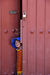 South America, Bolivia, Calamarca. Boy peeks through door in Calamarca.