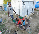 A boy pushes his friend in a wheel barrow  in a camp in Grand-Goave, Haiti, for families left homeless by the January 2010 earthquake. The ACT Alliance has supported families in this camp with a variety of services, and has rebuilt a school beside the tent city.