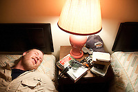 An angler lies on a bed in a small motel during a fishing road trip to the Driftless Area of southwestern Wisconsin.