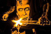 A glass blower creates his art with a Frankenstein t-shirt on.