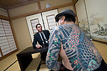 """Jake Adelstein, a former reporter at Japan's largest daily newspaper, Yomiuri Shimbun, author of """"Tokyo Vice"""" speaks with his bodyguard, a former yakuza mobster who goes by the name """"Mochizuki,"""" at an undisclosed location in Japan on Aug. 29, 2008. In 2005 American Adelstein uncovered a scandal involving senior members of Japan's mafia, the yakuza, visiting a medical center in Los Angeles to undergo liver transplants, despite being bared from entry due to having criminal records or suspected affiliation with Japanese organized crime groups. Within days, however, Adelstein was visited by mob members and told to either """"erase the story or be erased."""" He took the former option and resigned from the Yomiuri, though a recent leak of his story has pushed Adelstein and his family into hiding..Photographer: Robert Gilhooly"""