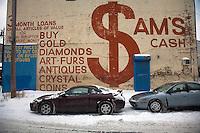 Detroit: paesaggio urbano con la neve. Due automobili parcheggiate e dietro un muro su cui c'è una grossa pubblicità di un banco dei pegni.