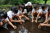 Bapak Juanda Datundugon helping children to plant mangrove seedlings during an environmental education class, Dudepo, Bolmong Selatan, Sulawesi, Indonesia.