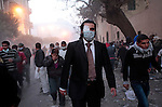 Protester wearing tie and suit run from tear gas cloud on Mohamed Mahmoud street near Tahrir Square during stand off and clashes with riot police on November 22, 2011 in Cairo, Egypt.