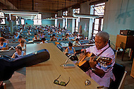 Cuba, March 1992: A former Torcedor(cigar roller) , Oscar Ramirez plays every afteroon to his former workmates who join him in chorus, in La Corona, The largest Cigar factory in Havana.