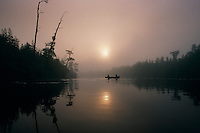 Fishermen break the still waters of Billy's Lake on a foggy morning in the Okefenokee Wildlife Refuge. A mysterious aura surrounds the Okefenokee which means &quot;land of the trembling earth&quot; in a Native American language. <br />