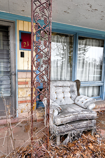 Room 21 has a weathered chair sitting outside, waiting. This abandoned motel out on the edge of the boondocks is the place where the Sandman meets the wandering fairy around midnight to share secrets when no men can hear. No living creatures ever come close to the place. The wind is the only visitor that comes by, blowing straight through and never staying, only carrying leaves and stray spooks. Even they won't stop and stay now that the cable has been shut off.<br /> <br /> Photographed exactly as it was found, the place sits not far but still out of sight from the four lane highway that killed the business and sent the maid home early. The world is still bypassing this place at 65 mph and no retro revival in the future will ever rejuvenate it. None of those modern drivers will ever get to see a slice of the Americana that came before on that mountain top ex-main road.<br /> <br /> The wrought iron grapes gave this image a title, which might be fitting depending on point of view. The motel is from the mid-sixties with a few facelifts in the past. Location: off the beaten path in the central Pennsylvania highlands, snow country, photographed with special permission.