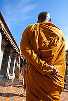 A monk from nearby Wat Suan dok, which is home to a large population of resident monks, walks with laypeople at Wat Pra That Doi Suthep in Chiang Mai, Thailand.