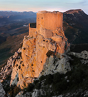 "Queribus Castle or Chateau de Queribus, Cathar Castle, Cucugnan, Corbieres, Aude, France. Evening view showing the steep rocky cliffs of its hilltop location and Pyrenees in the distance. The castle, built from 13th to 16th centuries, is considered the last Cathar stronghold. It sits on a high peak at 728m. It is one of the ""Five Sons of Carcassonne"" or ""Cinq Fils de Carcassonne"". It is a listed monument historique and has been fully restored, restoration work being completed in 2002. Picture by Manuel Cohen"
