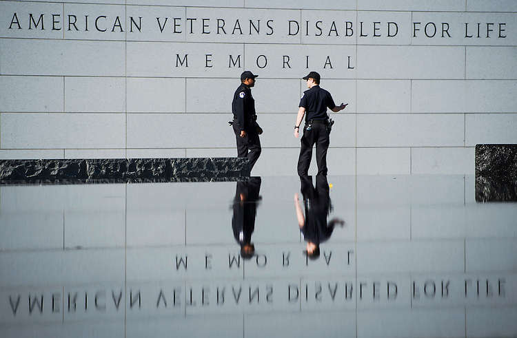 UNITED STATES - NOVEMBER11: Two U.S. Capitol Police officers walk past the American Veterans Disabled for Life Memorial in Washington on Veterans Day, Tuesday, Nov. 11, 2014. A large contingent of U.S. Capitol police were deployed around the east end of the National Mall in preparation for the Concert for Valor. (Photo By Bill Clark/CQ Roll Call)
