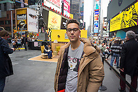 """Artist Justin Bettman in front of his  #SetintheStreet, an interactive film set in the middle of Times Square in New York on Friday, April 17, 2015. Created by Bettman, the public art project made out of found items allows visitors to pose for photos in a """"film still"""". The project in Times Square is in collaboration with the Tribeca Film Festival. Between uses found materials and hopes that #SetintheStreet will cause people to re-evaluate their thinking about trash.  (© Richard B. Levine)"""