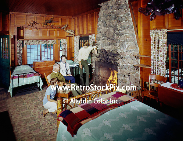 American Legion Mountain Resort. Family sitting by the fireplace in a motel room.