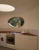 The curved oval window in this kitchen reflects the curves of this 1930s building, as does the circular skylight above