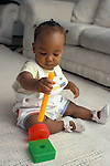 Richmond, CA African American baby twelve months old experimenting with eye-hand coordination trying to insert rod into plastic block  MR