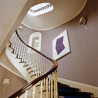 The cantilevered staircase winds elegantly up through the centre of the house