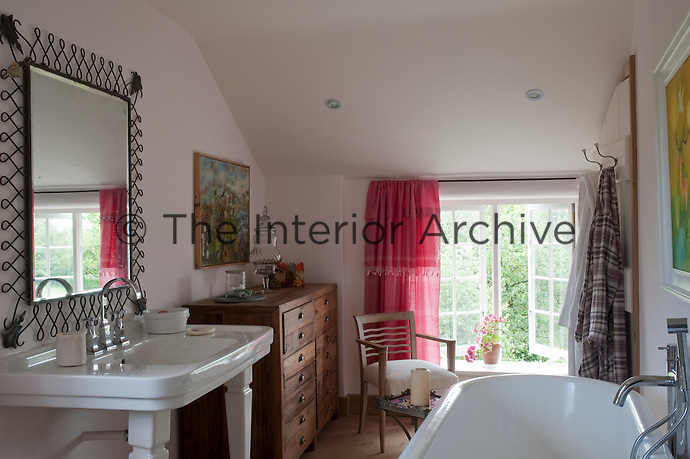 The bathroom is decorated with several splashes of colour including curtains made from Moroccan sheets which Carina dyed pink