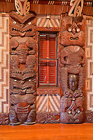 Carved Traditional Maori Figures, called Poupou, supporting the overhead rafters of the meeting house.  These are the fourth and fifth on the left side after entering the house.  The fifth represents the Ngai Te Rangi tribe of Tauranga.  The small head between the legs shows the extent of tattooing on women's faces in earlier times.   Te Whare Runanga, built 1940, Waitangi Treaty Grounds, Paihia, north island, New Zealand.  The woven panels on either side of the poupou are called tukutuku.  These are comprised of vertically-placed toetoe reeds (kakaho) across which lie narrow laths (kaho), laced through with colored strips of pingao grass and kiekie.