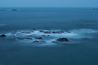 Waves break over reefs of rocks in the blue dusk along the coast of the Kii Peninsula, Japan.<br />