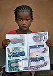 Three-year old Naomi Wallet Tafaki displays an album of family photographs in a Catholic training center in Niamana, Mali. Several families displaced by the fighting in northern Mali took refuge in the center, and have received support from the ACT Alliance.