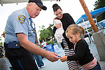 Officer Hurley hands a police sticker to 2-year old Tennysen during National Night Out at Rosita Park in Los Altos, CA August 6.